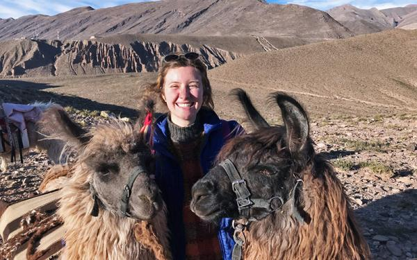 Student with two llamas in a foreign country